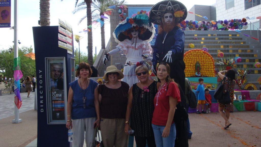 four writer friends in front of Dia De Los Muertos skeletons on stilts