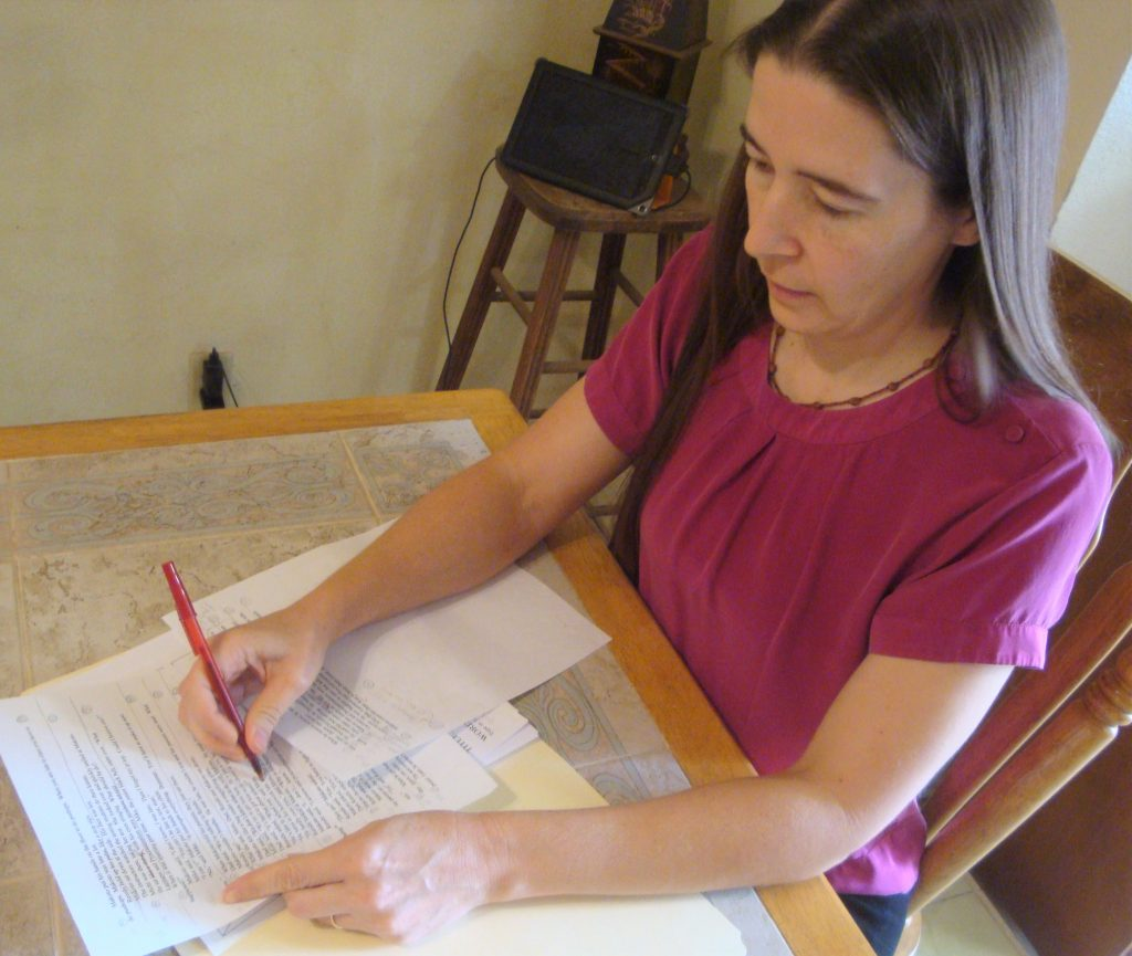 the writer editing a manuscript with a red pen