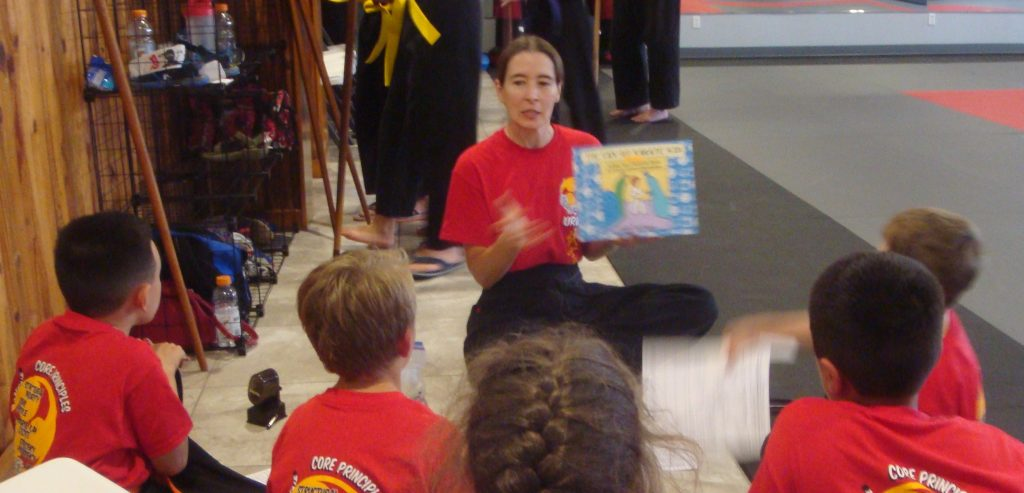 The author helping kids build character at a book reading.